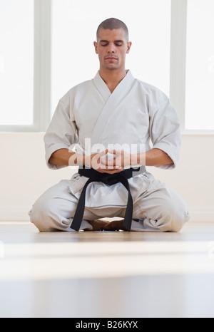 Hispanic male karate black belt meditating - Stock Photo