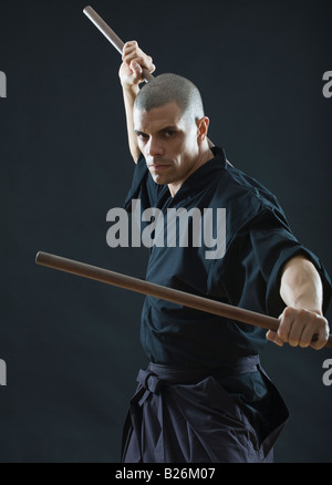 Hispanic male holding sticks in fighting stance - Stock Photo