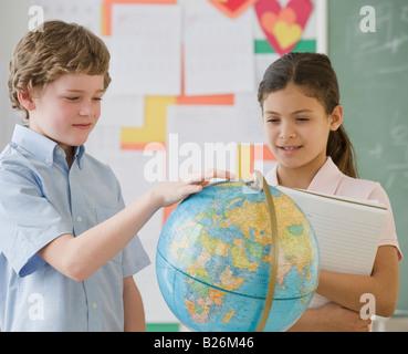 Multi-ethnic school children looking at globe - Stock Photo