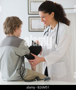 Hispanic female doctor taking child's blood pressure - Stock Photo