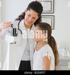 Hispanic female doctor weighing child - Stock Photo