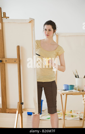 Woman painting on easel - Stock Photo