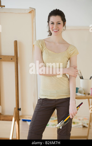 Woman holding paintbrushes in front of easel - Stock Photo