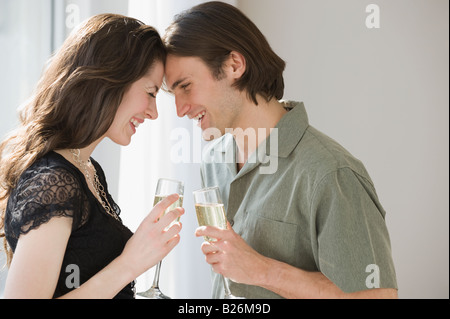 Couple holding champagne and touching foreheads - Stock Photo