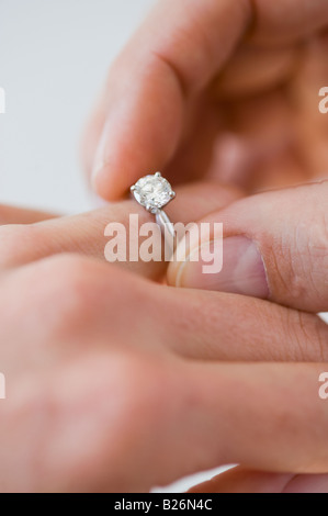 Man putting engagement ring on woman's finger - Stock Photo