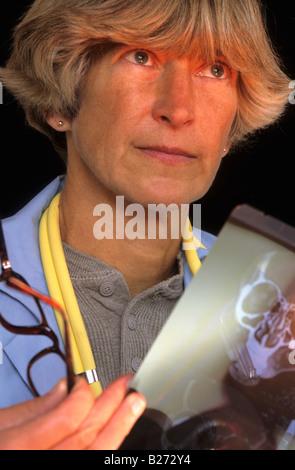 FEMALE PHYSICIAN STUDYING X RAY IMAGE - Stock Photo