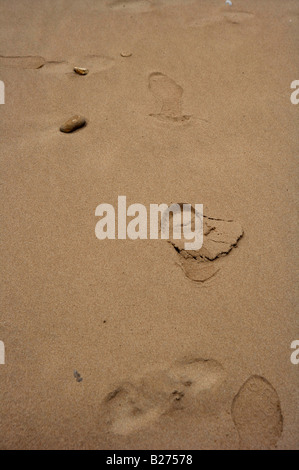 Footsteps in the sand on Omaha Beach in Normandy France with pebbles - Stock Photo