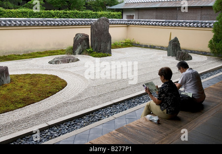 Couple sitting on veranda at Daitokuji Temple Ryogenin dry landscape rock garden contemplating rocks and raked gravel - Stock Photo