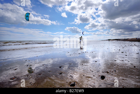 kite surfer on Goring beach near Worthing silhouetted against the sky and beach reflection. Picture by Jim Holden. - Stock Photo