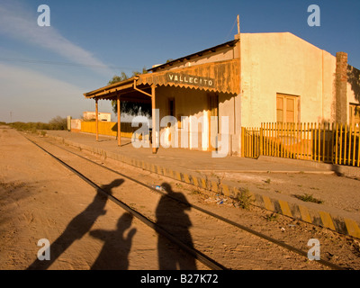 Abandoned train station in western Argentina with shadows of three people - Stock Photo