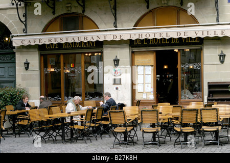 A couple of Genevoise take coffee at an open air cafe in Geneva very early in the spring - Stock Photo