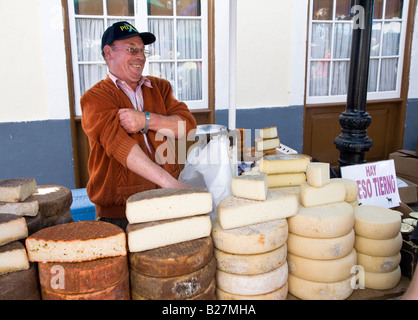 Man selling local cheese Flor de Guia made from sheep and goat's milk in Sunday market Teror Gran Canaria Spain - Stock Photo