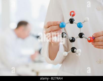 Female scientist holding molecular model - Stock Photo