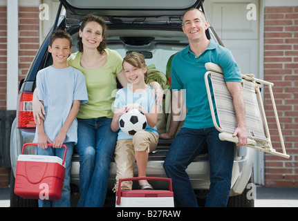 Family holding coolers and beach chair behind car - Stock Photo