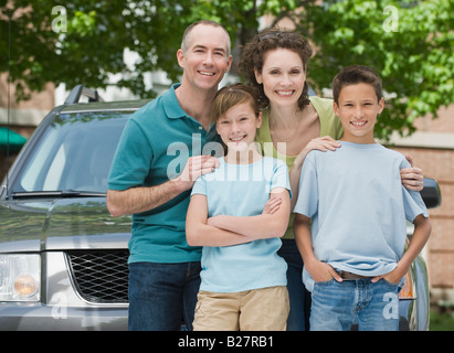 Family with two children in front of car - Stock Photo