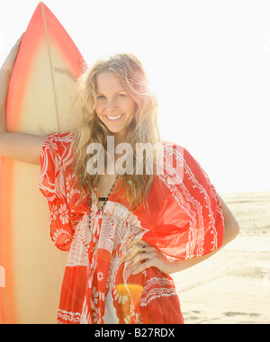 Woman holding surfboard on beach - Stock Photo