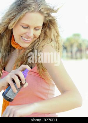 Woman spraying on sunscreen - Stock Photo