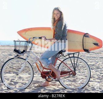 Woman with bicycle and surfboard on beach - Stock Photo