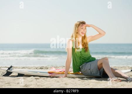 Woman sitting on surfboard - Stock Photo