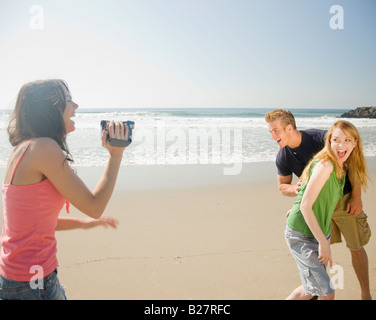 Woman video recording friends at beach - Stock Photo