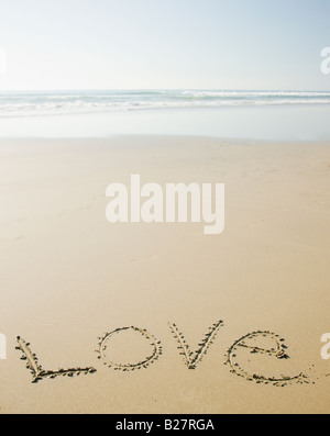 Love written in sand - Stock Photo