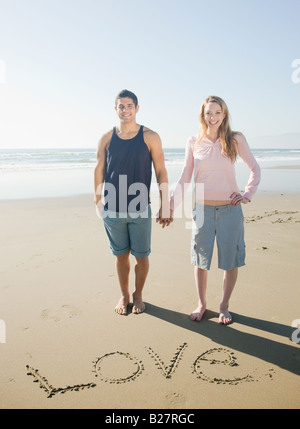 Couple next to Love written in sand - Stock Photo