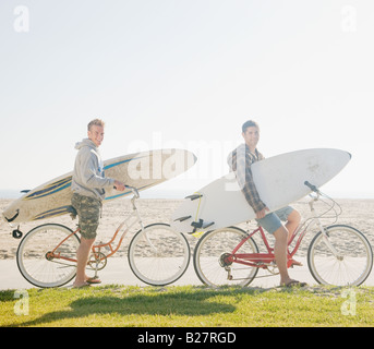 Two men with surfboards on bicycles - Stock Photo