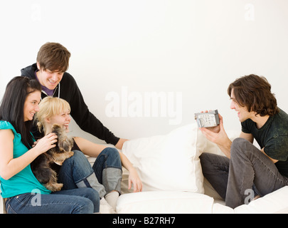 Man video recording friends on sofa - Stock Photo