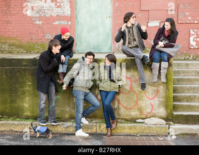 Group of friends sitting in urban scene - Stock Photo
