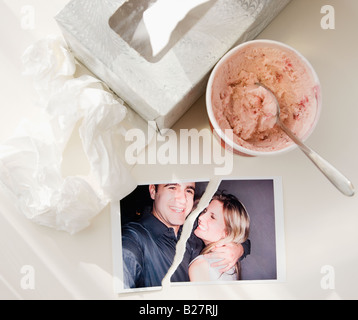Ripped photograph next to ice cream and tissues - Stock Photo