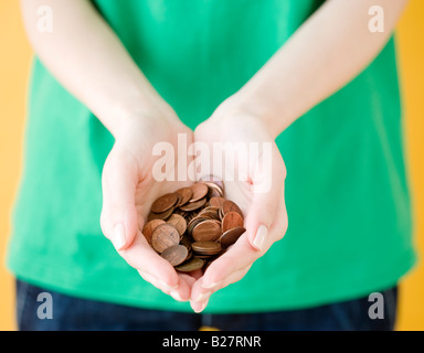 Woman holding handful of pennies - Stock Photo
