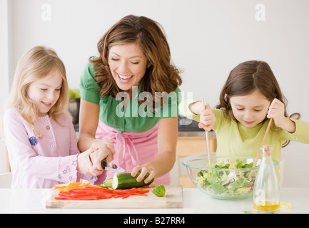 Mother and daughters preparing food - Stock Photo