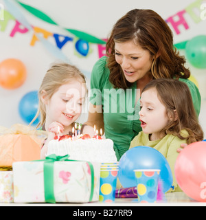 Girl celebrating birthday with mother and sister - Stock Photo