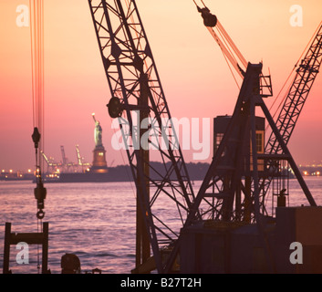 Crane with Statue of Liberty in background, New York, United States - Stock Photo