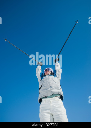 Woman holding ski poles over head - Stock Photo