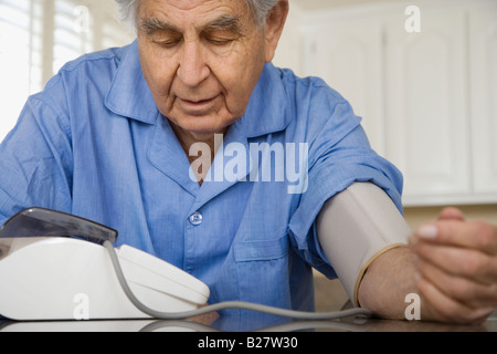 Senior man taking own blood pressure - Stock Photo