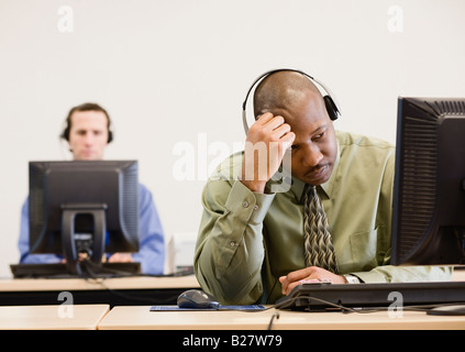 African businessman wearing headset - Stock Photo