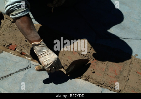 The gloved hands of a Mason using a trowel to place mortar between clay bricks making the edge a backyard patio - Stock Photo