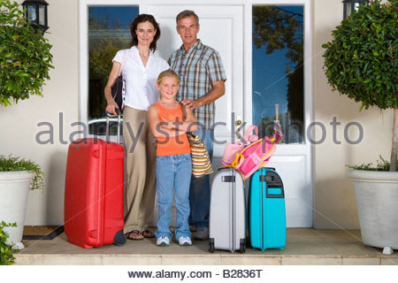 Family of three with luggage by front door, smiling, portrait - Stock Photo