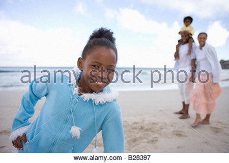 Girl (7-9) on beach with hand on hip, smiling, portrait, family in background - Stock Photo