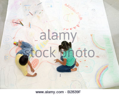 Brother and sister (6-10) drawing on large piece of paper on floor, elevated view - Stock Photo
