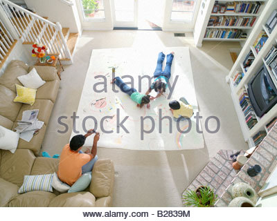 Family of four in living room, mother, son and daughter (6-10) drawing on large piece of paper on floor, elevated - Stock Photo