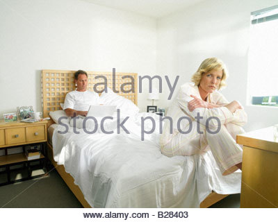 Portrait of woman on edge of bed in pyjamas by man using laptop computer in bed - Stock Photo