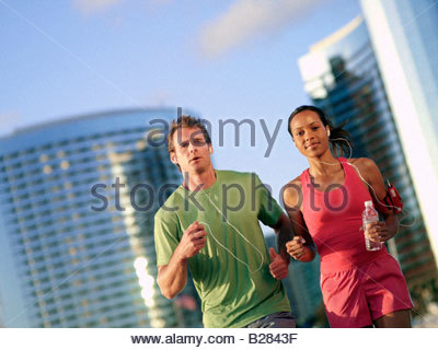 Young couple with earphones running by skyscrapers, portrait, low angle view - Stock Photo