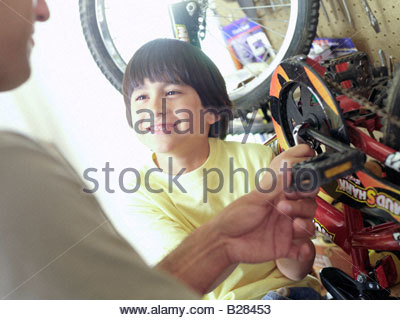 Father and son (7-9) fixing bicycle in garage, close-up of boy smiling - Stock Photo
