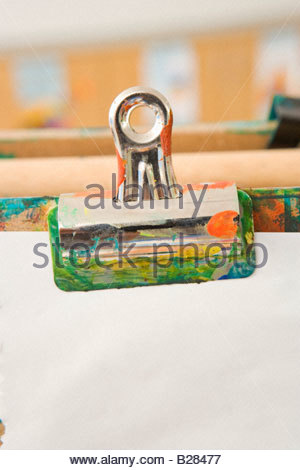 Bulldog clip holding paper on easel - Stock Photo