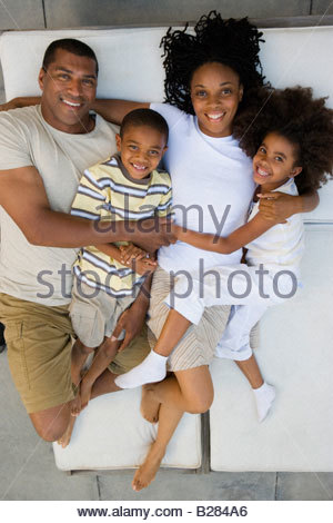 Family of four embracing on lounge chairs, smiling, portrait, elevated view - Stock Photo