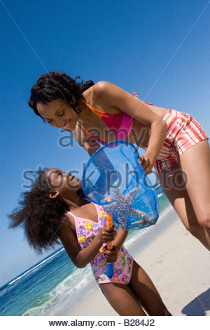 Mother and daughter(4-6) with fishing net on beach (tilt) - Stock Photo