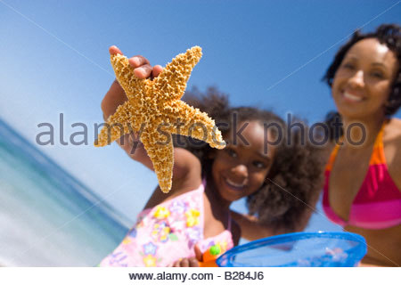 Mother and daughter(4-6) with starfish on beach (tilt) - Stock Photo