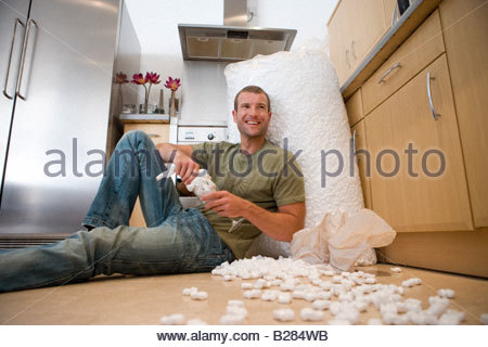 Man in kitchen packing glasses, smiling - Stock Photo